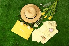 Composition with stylish women`s clothes and accessories for spring on green grass. Flat lay stock images