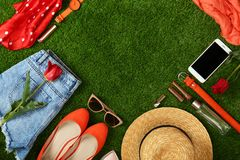 Composition with stylish women`s spring clothes and accessories on green grass, flat lay. Space for text stock photography