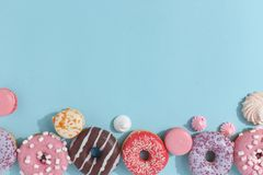 Composition of sweet glazed donuts and sweets on a blue background. Top view. Concept of children's holiday. Space for copy. Dessert food sprinkles stock image