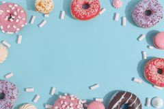 Composition of sweet glazed donuts and sweets on a blue background. Top view. Concept of children's holiday. Space for copy. Dessert food sprinkles royalty free stock image