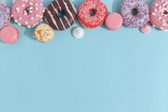 Composition of sweet glazed donuts and sweets on a blue background. Top view. Concept of children's holiday. Space for copy royalty free stock images