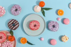 Composition of sweet glazed donuts and sweets on a blue background. Top view. Concept of children's holiday. Space for copy royalty free stock photo