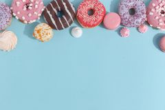 Composition of sweet glazed donuts and sweets on a blue background. Top view. Concept of children's holiday. Space for copy stock photo