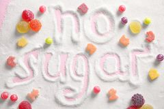 Composition with sweets and phrase NO SUGAR. Written on sugar sand royalty free stock photography