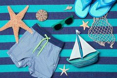 Composition with swimming trunks and sunglasses. On color background Stock Photos