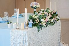 Closeup bouquet flowers rose delphinium wedding. The composition on the table with a tablecloth and delphinium roses with green leaves and a candle with Royalty Free Stock Photo