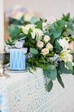 Closeup bouquet flowers rose delphinium wedding. The composition on the table with a tablecloth and delphinium roses with green leaves and a candle with Stock Images