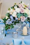 Closeup bouquet flowers rose delphinium wedding. The composition on the table with a tablecloth and delphinium roses with green leaves and a candle with Stock Photos
