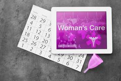 Composition with tablet, menstrual cup and calendar on grey background. Gynecological care. Flat lay composition with tablet, menstrual cup and calendar on grey royalty free stock image