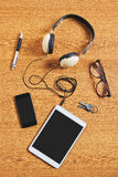 Composition of tablet, phone and headphones on a desk. Royalty Free Stock Images