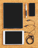 Composition of tablet, phone and headphones on a desk. Stock Photos