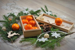 Composition with tangerines in a wooden box and garlands Stock Images