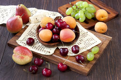 Composition with tasty fruits. Colorful summer fruits - cherries,  apricots, pears and grape  on wooden table Royalty Free Stock Photography