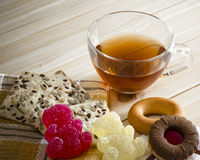 The composition of the tea beverage in a large bowl and some sweets. On the table. Candied fruit jelly, cereal biscuits, bagels and biscuits with marmalade Stock Photos