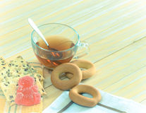 The composition of the tea beverage in a large bowl and some sweets. On the table. Fruit jelly, cereal biscuits, bagel royalty free stock image