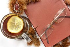 Composition. Tea with lemon, a closed book, glasses and chestnuts stock photography
