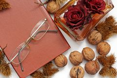 Composition. Tea with lemon, a closed book, glasses and chestnuts royalty free stock image