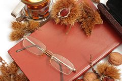 Composition. Tea with lemon, a closed book, glasses and chestnuts royalty free stock photos