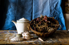 Composition of a teapot, basket full of withered flowers and clams Stock Images