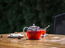 A summer fruit tea with fresh strawberries and natural currant on a wooden background. Healthful and organic breakfast. A composition of a teapot full of Stock Photography