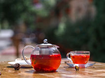 A summer fruit tea with fresh strawberries and natural currant on a natural background. Healthful and organic breakfast. A composition of a teapot full of Stock Photo