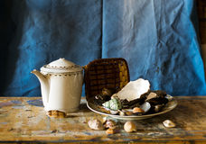 Composition of a teapot, little basket and a plate filled with clams Stock Image