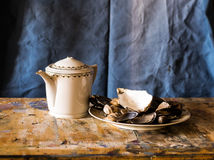 Composition of a teapot and a plate filled with clams Stock Photo