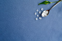 The composition of a teaspoon of sugar and plant leaves on a blue background Stock Images