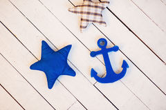 Composition with textile starfish and anchor. Composition with textile starfish and anchor set on white wooden table, relaxation by sea concept Stock Images