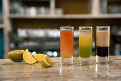 A composition of three colorful shot drinks. Alcoholic cocktails with lime on a bar background. royalty free stock photo
