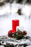 The composition of the three decorative candles and twigs with berries and cones on a snow-covered tree stump in the woods. Stock Image