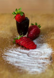 Composition of three strawberries, sugar and a glass filled with marmalade Stock Images
