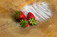 Composition of three strawberries and sugar Stock Image