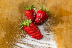 Composition of three strawberries and sugar Royalty Free Stock Photo