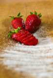 Composition of three strawberries and sugar Royalty Free Stock Image