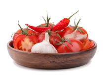 Composition of tomato bunch and chili pepper and garlic on a wooden plate royalty free stock images