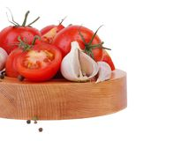 Composition of tomato bunch and chili pepper on a wooden plate royalty free stock photo