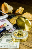 Composition of tourist compass,money,shells and fotocamera on the wooden table Stock Photos
