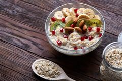 Composition with bowl of oatmeal porrige and dry oatmeal in glassware on vintage wooden table, selective focus. Composition with transparent bowl of oatmeal Royalty Free Stock Images