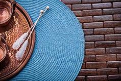 Composition of tray tea cups sugar sticks wicker. Table cloth stock photos
