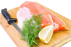 Composition of trout fish fillet with knife on a kitchen board Royalty Free Stock Images