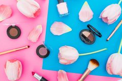 Composition with tulips flowers and cosmetics on bright background. Top view. Flat lay, home feminine desk. Composition with tulips flowers and cosmetics on royalty free stock photo