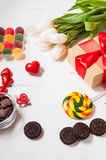 Composition with tulips, sweets, candies and gift box. valentine`s or mother` day. Stock Photos