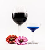 Composition of two cocktails - black and blue and flowers on a white background.  Stock Image