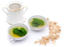 Composition with two cups of mint tea and brown cane sugar Stock Images