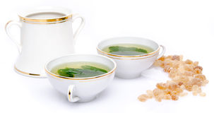 Composition with two cups of mint tea and brown cane sugar Stock Photography