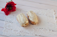 Composition of two eclairs with white chocolate and red poppy flower on table Royalty Free Stock Photography