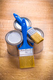 Composition of two paint brushes and three cans on. Wooden board Royalty Free Stock Images
