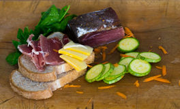 Composition of two slices of bread, salami, cheese, courgettes, spinach and pieces of carrot Royalty Free Stock Image