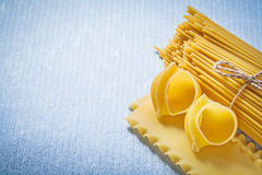 Composition of uncooked macaroni products on blue background foo Stock Photo
